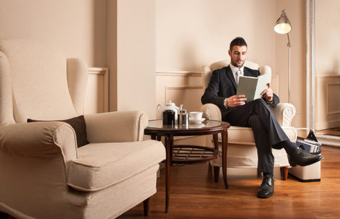 Young businessman relaxing reading a book