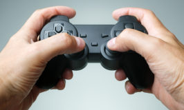 Video game console controller in gamer hands