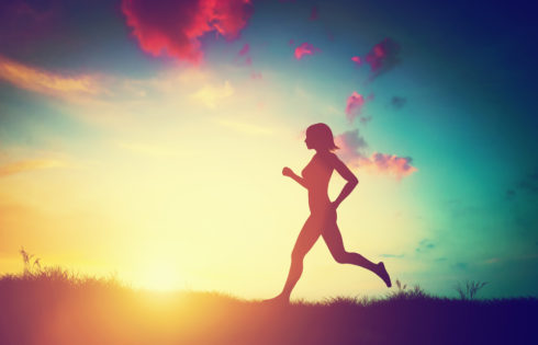 Silhouette of a fit woman running at sunset