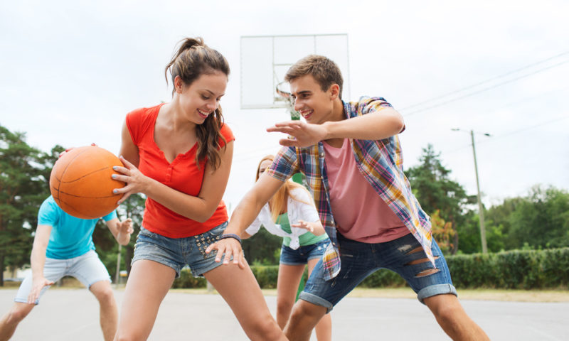 Happy teenagers playing basketball outdoors